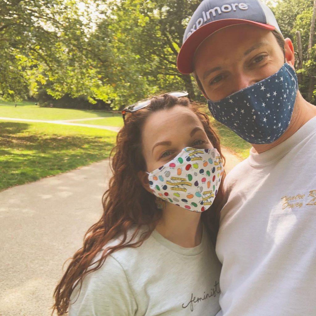 Rebecca and her boyfriend JJ smiling behind masks on a sunny day in the park. Rebecca's mask is covered in Bertie Bott's Every Flavour Beans and JJ's is blue with white stars.