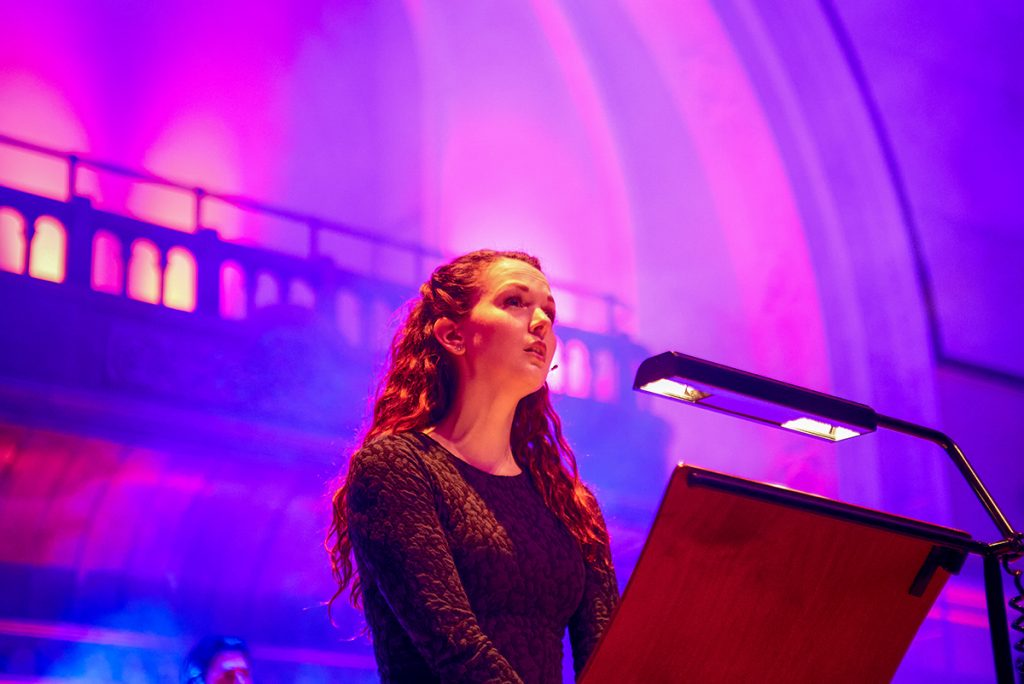 Rebecca stands at a wooden music stand wearing a black and green long sleeve dress. She has long curly auburn hair and is illuminated by red light. Behind her, the hall is illuminated in purple and pink light.