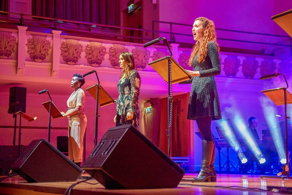 Sharon Rose, Lucie Jones, and Rebecca stand in a line, singing, at music stands. Sharon wears a tan jumpsuit and Lucie wears a black floral dress.